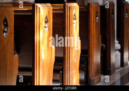 Church interior. Row of church pews lit by early morning sun. - Stock Photo