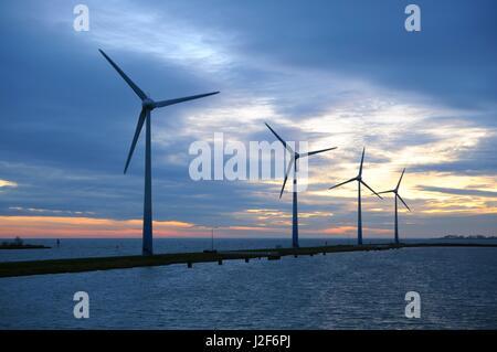 Wind turbines at sunset in IJsselmeer - Stock Photo