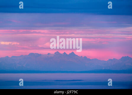 Sunrise as seen from the top of the Lusen mountain in the Bavarian Forest National Park with the european alps on - Stock Photo