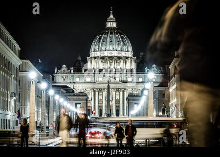 View of illuminated Saint Peter Basilica, Street Via della Conciliazione and light trails of cars in Rome, Italy - Stock Photo