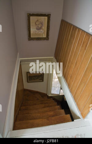 Opened trap door and wooden staircase leading from upper floor to downstairs floor inside an old 1877 cottage style - Stock Photo