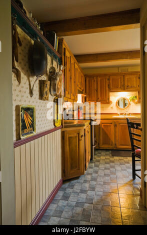 Hallway leading to rustic kitchen with wooden cabinets inside an old reconstructed 1850s cottage style log home - Stock Photo