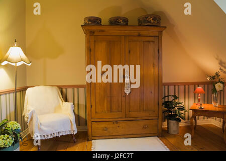White throw over sitting chair and antique wooden armoire in master bedroom on upstairs floor inside old reconstructed - Stock Photo