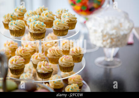 Vanilla bean mini cupcakes decorated with cyan and pink candy beads on clear tiered tray on a dessert table with - Stock Photo