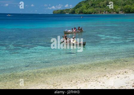Melanesia, Solomon Islands, Santa Cruz Island group, Malo Island. Clear shallow bay and coral reef, villagers in - Stock Photo