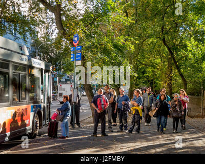 A diversified crowd of travelers waits at a southbound bus stop by Central Park on Fifth Avenue, NY City, on a sunny - Stock Photo