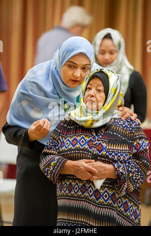 Wearing a hijab or head scarf, a Muslim woman talks to an older relative before religious services at an Anaheim, - Stock Photo