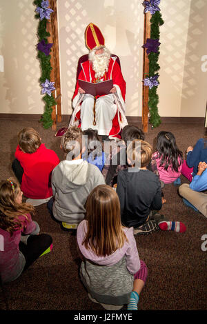 An actor costumed as Saint Nicholas and wearing a mitre reads Christmas stories aloud to children during Advent - Stock Photo