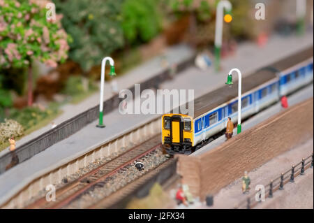 miniature model commuter train in a station with shallow d.o.f - Stock Photo
