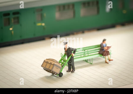 miniature figure of a railway staion porter moving luggage - shallow d.o.f. - Stock Photo
