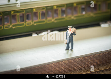 miniature model of a sailor alone on a railroad platform - shallow d.o.f. - Stock Photo