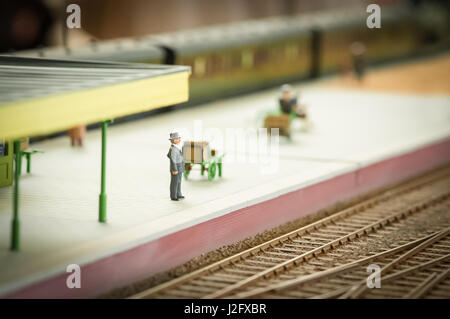 miniature model of a well dressed man waiting for a train - shallow d.o.f - Stock Photo