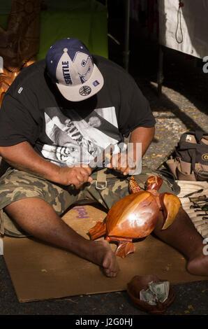 USA, Hawaii, Oahu, Honolulu. Artisan carves wooden sea turtle at the Aloha Stadium Swap Meet. (For Editorial Use - Stock Photo