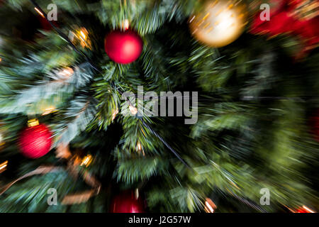 zoom blast (motion blur) shot of red and gold christmas decorations and fairy lights on a christmas tree - Stock Photo