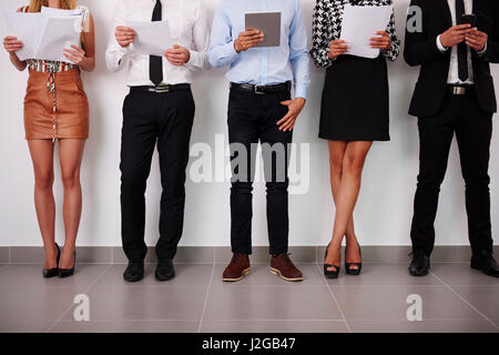 Human legs of people which waiting for job interview - Stock Photo
