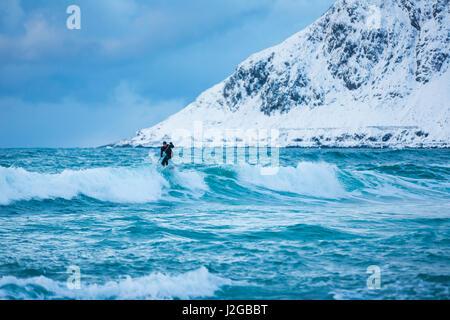 Flakstad, Norway - March 18 2017: Surfer are training on the Skagsanden beach of the Lofoten Islands - Stock Photo