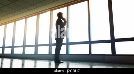 Full length shot of businessman standing near office window and talking on mobile phone. Man looking outside the - Stock Photo