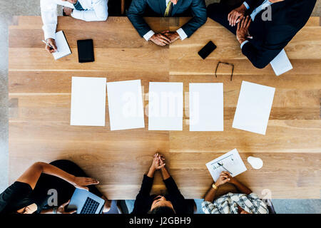 Top view of office workers sitting around a table in conference room. Multi-ethnic business people in meeting with - Stock Photo