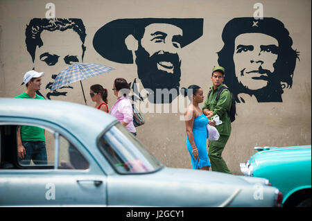 HAVANA - JUNE, 2011: Colorful vintage American cars and pedestrians pass in front of a propaganda mural featuring - Stock Photo