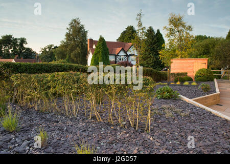 Beautiful, private garden, Yorkshire, England, UK - stylish, contemporary design, hard landscaping (paving) shed - Stock Photo