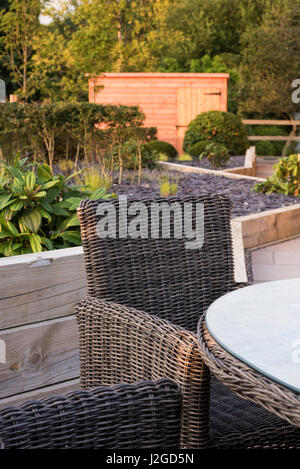 Private, contemporary landscaped, garden, England, UK - close-up of chair in seating area (patio furniture) raised - Stock Photo