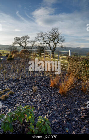 Sunny winter view of a corner of a beautiful private garden, Yorkshire, England, UK - herbaceous border with slate - Stock Photo