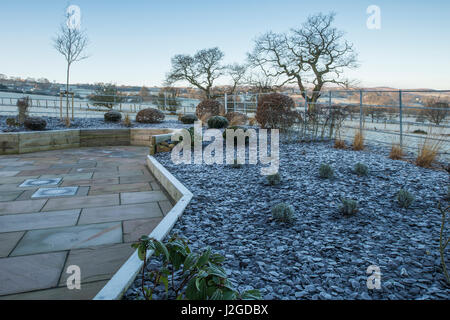 Winter frosty view of private garden, with stylish, contemporary design,  hard landscaping and new planting on raised - Stock Photo