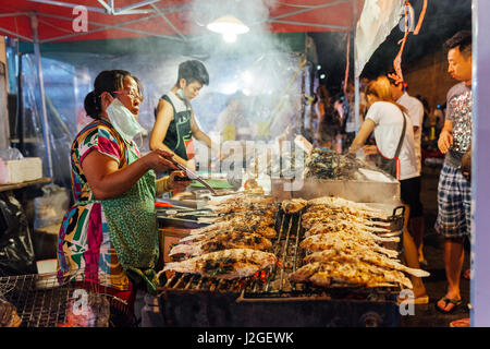 CHIANG MAI, THAILAND - AUGUST 27: Food vendor cooks fish and seafood at the Saturday Night Market (Walking Street) - Stock Photo