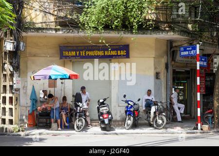 HANOI, VIETNAM - MAY 10: Barber is shaving man on the street on May 10, 2014 in Hanoi, Vietnam. - Stock Photo