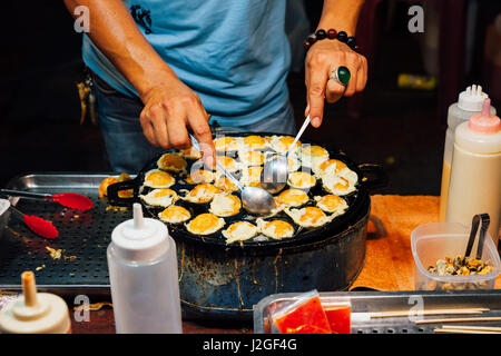 CHIANG MAI, THAILAND - AUGUST 21: Food vendor cook quail eggs at the Sunday Market (Walking Street) on August 21, - Stock Photo