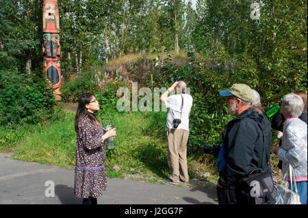 Native interpreter explaining a traditional totem pole to visitors, Anchorage, Alaska - Stock Photo