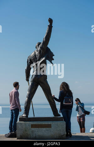 Tourists are posing for a photo with the statue of Freddie Mercury, late singer of the UK rock band Queen, at the - Stock Photo