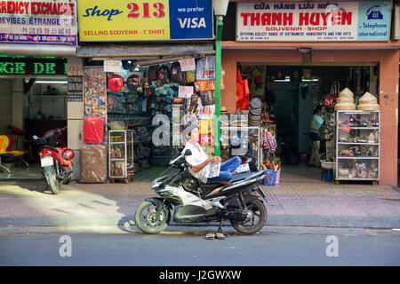 HO CHI MINH CITY, VIETNAM - MARCH 29: Man reading the newspaper while sitting on the motorbike on March 29, 2014 - Stock Photo