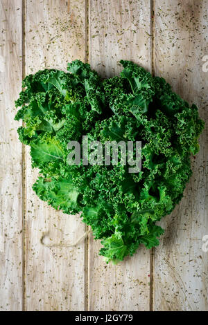 closeup of a bunch of kale leaves on a rustic wooden table - Stock Photo