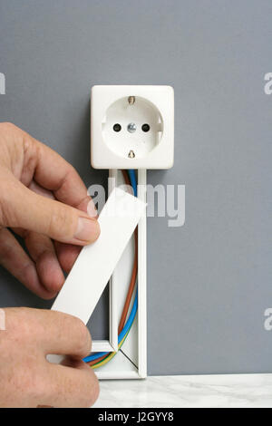 installing a power outlet with surface mount electric wiring channel rh alamy com Interior Wall Surface Wiring Surface Electrical Wiring