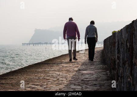 A man and a women walk along Teignmouth sea front railway path with the pier and The Ness rock in the background. - Stock Photo
