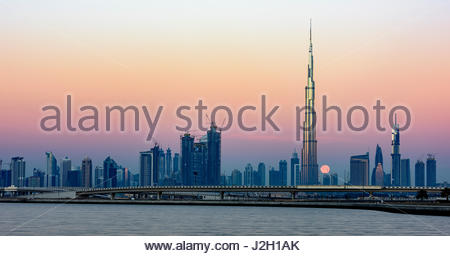 Moon passing behind Burj Khalifa, picture taken early morning from Al Jadaf - Stock Photo