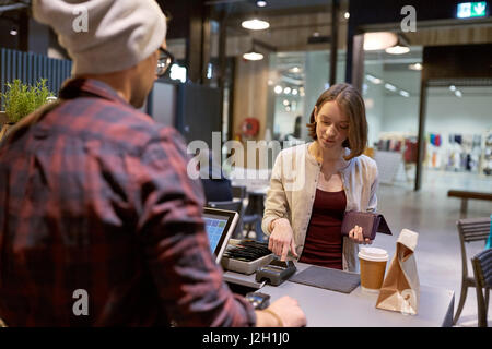 happy woman paying for purchases at cafe - Stock Photo