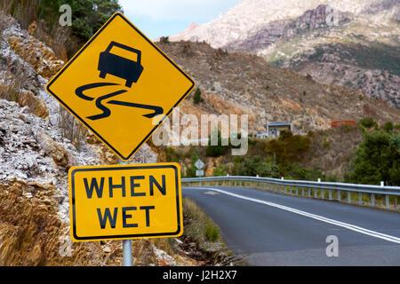 Slippery when wet sign in Tasmania, Australia - Stock Photo