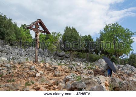 Europe, Balkans, Bosnia and Herzegovina, Medjugorje. A man praying near the wooden cross on the apparition hill - Stock Photo