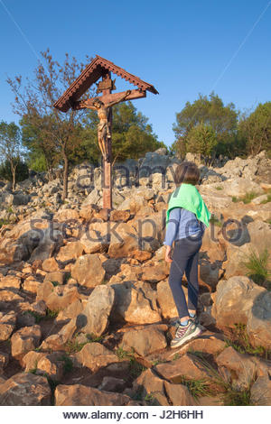 Europe, Balkans, Bosnia and Herzegovina, Medjugorje. A young girl on the apparition hill - Stock Photo