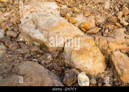 small rock formation in brown tones with lose rocks - Stock Photo