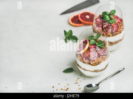 Greek yogurt, granola and blood orange layered parfait in glasses - Stock Photo