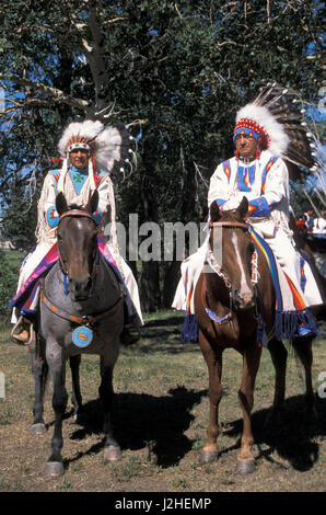 Two elder Blackfeet men dressed in traditional beaded and brain-tanned leather pants, shirts and eagle feather headdresses - Stock Photo