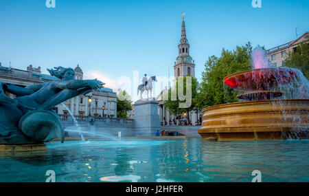 Fountains in Trafalgar Square with Equestrian statue of King George IV and St Martin-in-the-Fields church. London, - Stock Photo