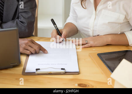 woman's hand hold ballpoint pen writing on  agreement paper sheet, fill in document template, applying for mortgage - Stock Photo