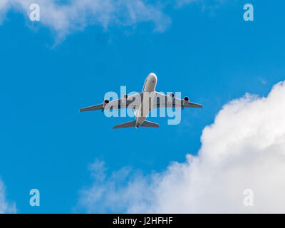 Jet passenger plane against blue sky with clouds seen from below. - Stock Photo
