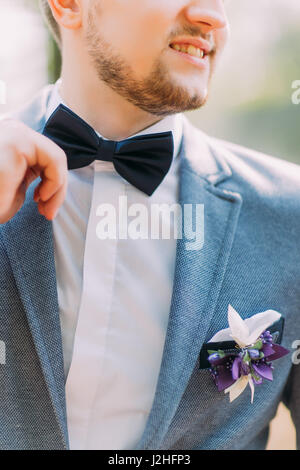 Man in blue suit with black bow tie, flower brooch, and classic texture pocket square, close up. - Stock Photo