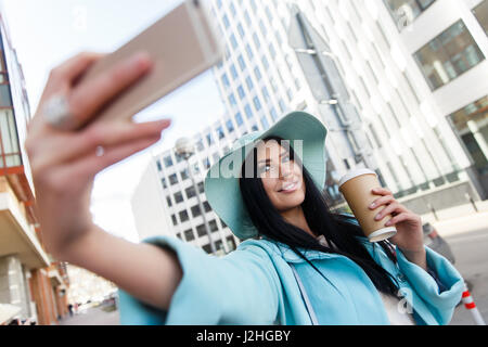 Brunette in hat takes pictures of herself on street - Stock Photo
