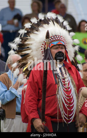 Mandan man dressed in traditional dress of an eagle feather headdress, red shirt and face paint symbolizing a high - Stock Photo